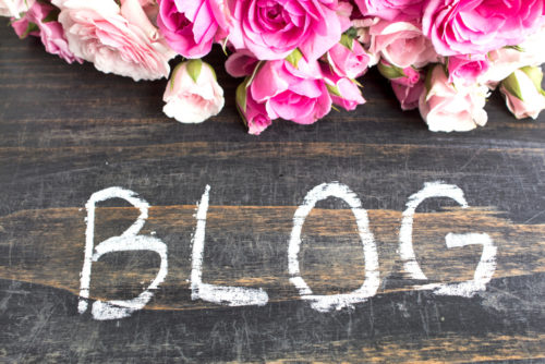 Word Blog with Pink Roses on a Rustic Wooden Background.