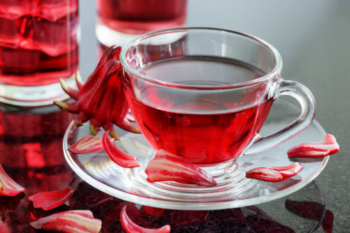 Cup of hibiscus tea (rosella, karkade, red sorrel, Agua de flor de Jamaica) on table. Drink made from magenta calyces (sepals) of roselle flowers. Healthy herbal tea rich in vitamin C and minerals.