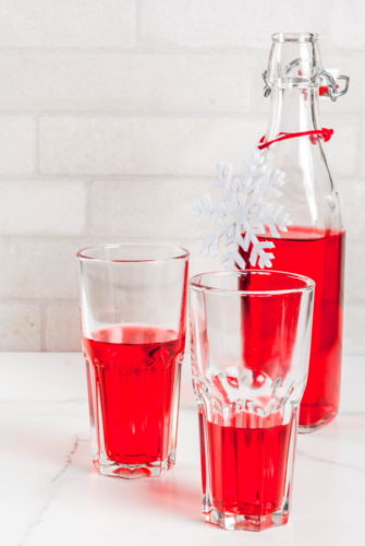 Autumn, winter drinks. Homemade cranberry juice, in a bottle and glasses on white marble table. copy space