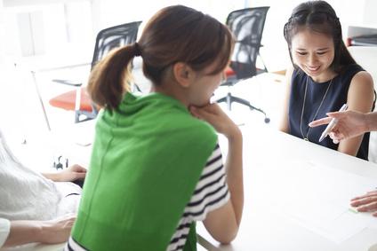 会議資料を見ながら話し合いを行うオフィス風景