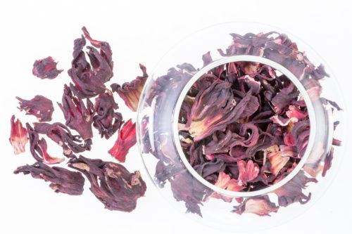 Overhead view of dried hibiscus tea leaves served in a glass bowl against a white background