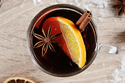 Mulled wine in a glass. A glass of drink is decorated with a cinnamon stick, a slice of lemon and anise. Light wooden background. Close-up. View from above.